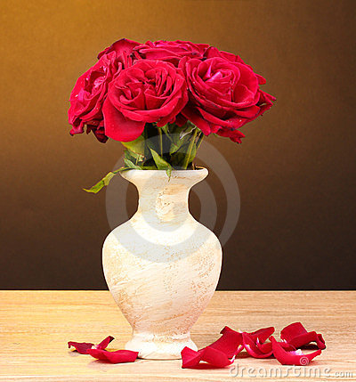 Beautiful red roses in vase on wooden
