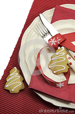 Beautiful red theme festive Christmas dining table place setting with Happy Holiday ornaments