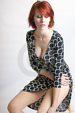 Beautiful redhead woman on a stool