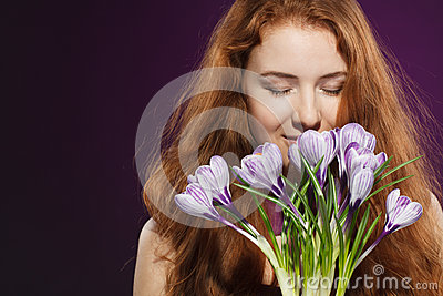 Beautiful redheaded female smelling the crocuses