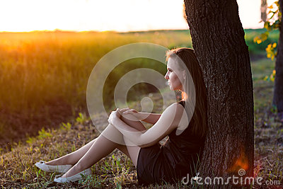 Beautiful relaxed woman sitting near the tree