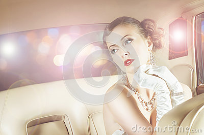 Beautiful and rich superstar girl sitting in a retro car