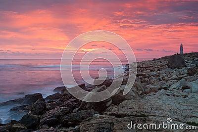 Beautiful rocky sea beach with lighthouse