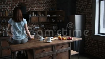 Beautiful romantic couple hugging in the kitchen. Beautiful romantic couple hugging while spending time together in modern kitchen in the morning. Back view of stock footage