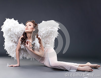 Beautiful sad woman posing in angel costume
