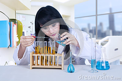 Beautiful scientist pouring liquid at lab