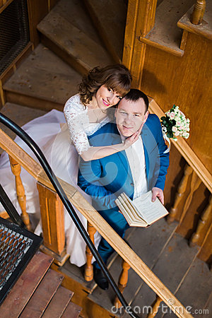 Free Beautiful Sensual  Bride Hugging From Behind Her Handsome Groom Holding Book At The Wooden Stairs Of Old Library Royalty Free Stock Photography - 71430897