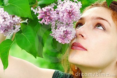 Beautiful sensual woman smelling lilac flower