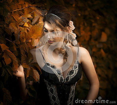 Free Beautiful Sensual Woman With Roses In Hair Posing Near A Wall Of Green Leaves. Young Female In Black Elegant Dress Daydreaming Royalty Free Stock Image - 64815396