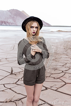 Free Beautiful, Sexy Blond Girl Posing In The Mountains On A Cracked Ground In A Black Hat With Bright Make-up Royalty Free Stock Image - 98710636