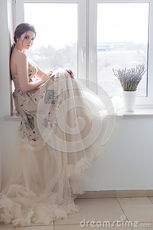 Free Beautiful Sexy Brunette Girl In Elegant Dress With Long Train With Lavender Flowers Stock Photo - 113970800