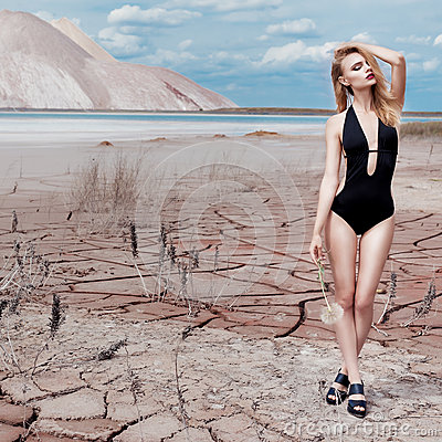 Free Beautiful Sexy Cute Girl In Swimsuit Fashion Shoot In Desert With Dry Cracked Ground Background Mountains Under Royalty Free Stock Photography - 56628267