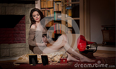 Beautiful sexy woman near a red gramophone surrounded by photo frames in vintage scenery. Portrait of girl in slim fit short dress
