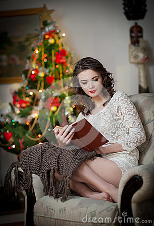 Beautiful sexy woman with Xmas tree in background reading a book sitting on chair. Portrait of a woman reading a book sitting