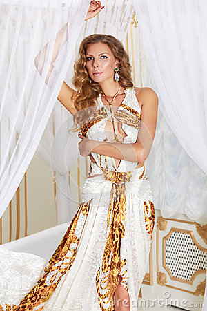 Free Beautiful Sexy Young Blonde Woman With Long Curly Hair And Make-up Wearing A Long Evening Dress White With Gold Embroidery And Jew Stock Photo - 46479130