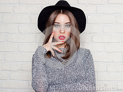 Beautiful young girl in a black hat with red full lips, bright makeup and painted my nails red Stock Photo