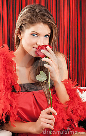 Beautiful sexy young woman smelling a red rose