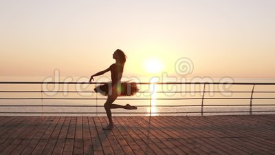 Beautiful silhouette of ballerina in ballet tutu and point on embankment above ocean or sea at sunrise. Young beautiful. Long haired woman practicing and stock video footage