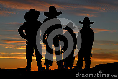 Beautiful silhouette of four young cowboys with a sunset backgro