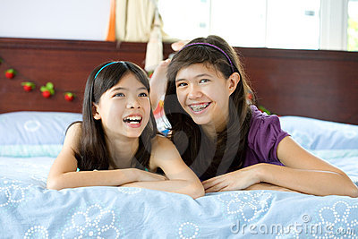 Beautiful sisters sharing a joke at home