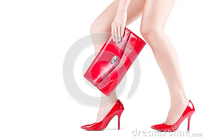 Beautiful slender womanish feet in red shoes