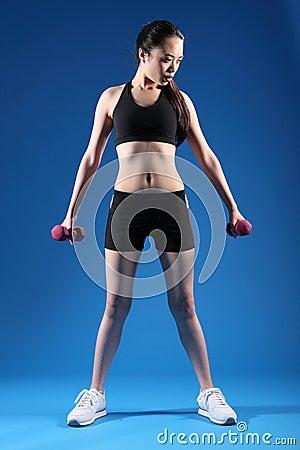 Beautiful slim asian girl using exercise weights
