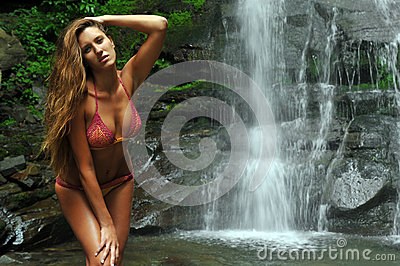 Beautiful slim fitness model posing sexy under waterfalls