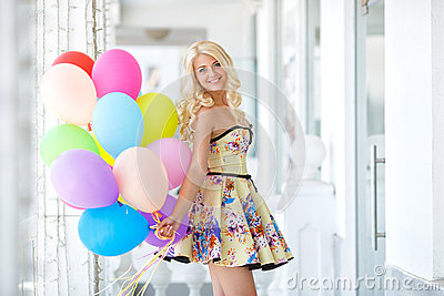 Beautiful smiling blond girl with colorful balloons