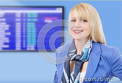 Beautiful smiling blond stewardess, boarding panel on background Stock Photo