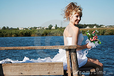 Beautiful smiling bride sitting on the bridge