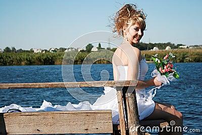 Beautiful smiling bride sitting on the bridge