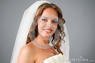 Beautiful smiling bride under veil in studio