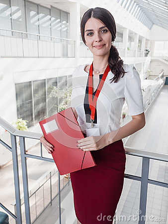 Free Beautiful Smiling Businesswoman Standing Against White Offices Background. Portrait Of Business Woman With A Folder In Her Hands Royalty Free Stock Photography - 95410417