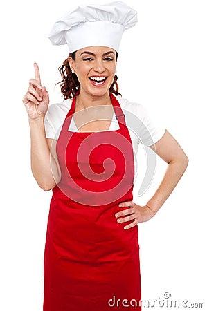 Beautiful smiling female chef indicating upwards