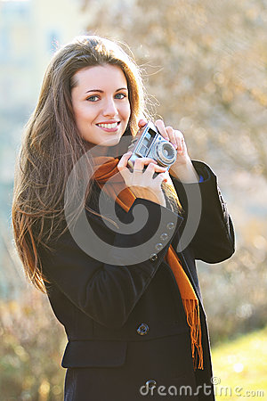 Beautiful smiling girl with old camera in hand