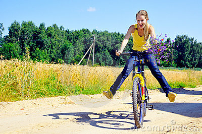 Beautiful smiling girl rides bicycle