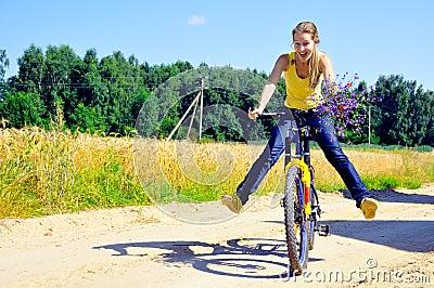 Beautiful smiling girl rides bicycle on village ro