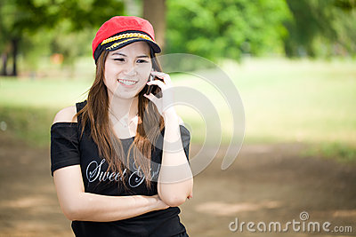 Beautiful smiling girl talks on cellular telephone outdoors