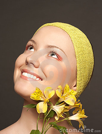 Beautiful smiling girl with a yellow flower