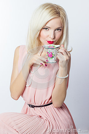 Free Beautiful Smiling Happy Sexy Elegant Girl With Red Lipstick In A Pink Dress In Retro Style Drinks Tea Coffee From A Small Mugs Stock Photo - 47153760