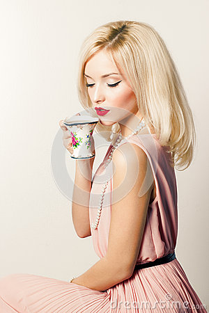 Free Beautiful Smiling Happy Sexy Elegant Girl With Red Lipstick In A Pink Dress In Retro Style Drinks Tea Coffee From A Small Mugs Royalty Free Stock Photo - 47153815