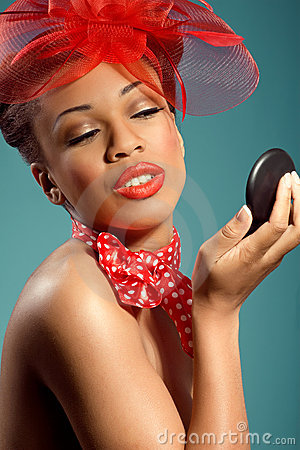Beautiful smiling pinup girl checking makeup