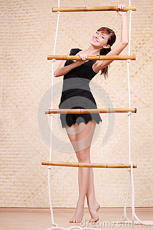 Beautiful smiling woman holds on bamboo rope ladder