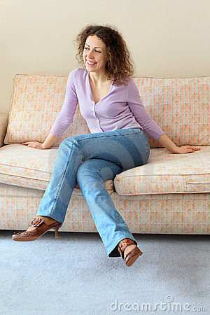 Beautiful smiling woman sits on couch
