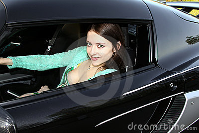 Beautiful smiling woman in sport car