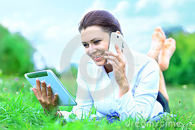 Beautiful smiling woman with tablet pc and talking on  mobile phone