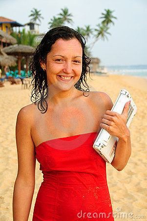 Beautiful smiling young woman with laptop on beach