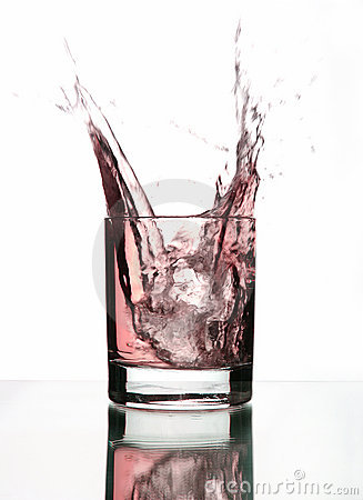 A beautiful splash of ice in a glass of pink water