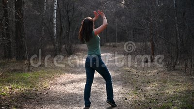 Beautiful summer girl in forest, standing in yoga pose on rug. Keeps balance, meditates, muscle stretching, outdoor stock footage