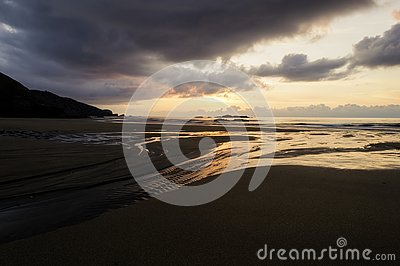 Beautiful summer golden sunset above the black sea with calm waves and reflection on the beach Stock Photo